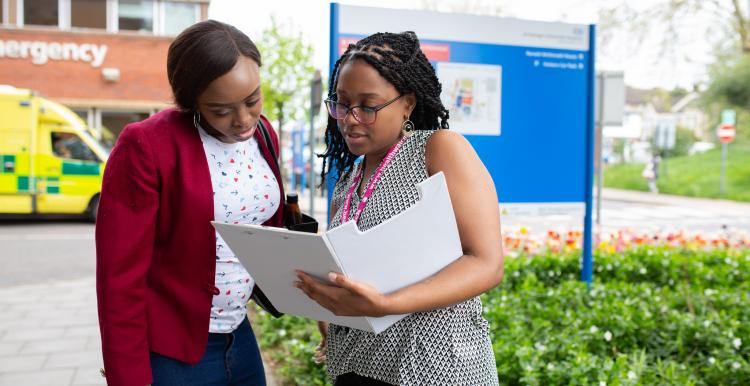 Women looking at file in front of hospital sign