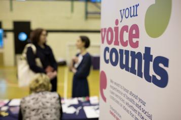 Women talking with Healthwatch 'your voice counts' sign in front at event