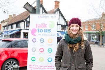 Young woman in front of Healthwatch sign