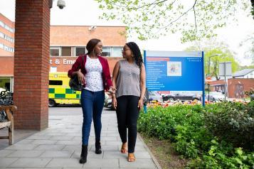 women walking in front of ambulance