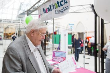 Elderly man at event reading leaflet