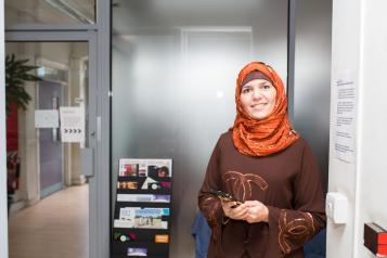 woman wearing a headscarf holding her mobile phone