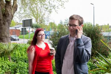 Man on the phone outside, standing next to a woman